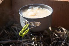 A closeup of a boiling pot on a gas primus cooking dinner for hikers. Stock Photos
