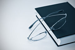 Closeup of book and glasses Stock Images