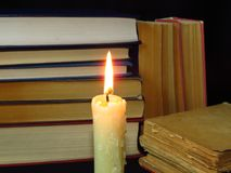 Old books stacked in a pile and a burning candle. Education, knowledge, reading habits, paper, library, light, flame, mystery. Closeup of books pile. A pile of stock images
