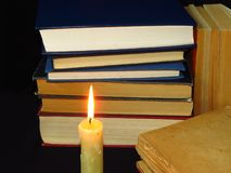 Old books stacked in a pile and a burning candle. Education, knowledge, reading habits, paper, library, light, flame, mystery. Closeup of books pile. A pile of royalty free stock images