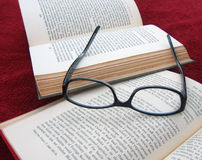 Closeup of books and  reading glasses. Closeup of woman's black reading glasses upside down on two open books Stock Photos
