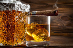 Closeup of bottle, glass with whiskey and smoldering cigar Royalty Free Stock Photos