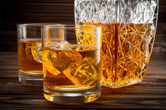 Closeup of bottle and two glasses with ice and whiskey Royalty Free Stock Image