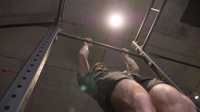 Closeup bottom up shoot of adult muscular athletic man lifting himself on the bars indoors in the gym stock footage
