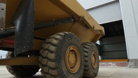 Closeup bottom view yellow tipper truck drives back to garage stock video footage