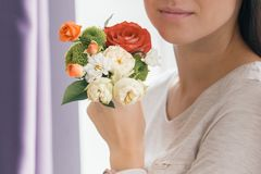 Closeup of bouquet flowers in hand young smiling woman royalty free stock photos