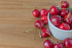 Closeup of a bowl of cherries with some fallen out. A closeup of a white bowl of fresh cherries on a wooden table top, with some of the cherries fallen out onto Stock Images