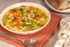 Closeup of a bowl of chicken noodle soup with rustic bread Stock Photo