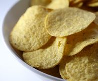 A Bowl of Crunchy Nachos on a White Table. Closeup of a bowl of delicious and crunchy nachos. Nachos are golden brown and the bowl and table are white royalty free stock photos