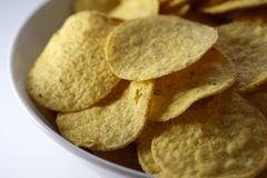 A Bowl of Crunchy Nachos on a White Table. Closeup of a bowl of delicious and crunchy nachos. Nachos are golden brown and the bowl and table are white stock photos