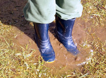 Closeup of boy in blue rain boots splashing in a muddy puddle af. Closeup of boy in blue rain boots splashing in a muddy puddle in the grass after the rain, sun Royalty Free Stock Photography