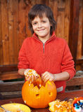 Closeup of boy carving Halloween jack-o-lantern Stock Images
