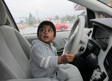 Closeup of a boy holding steering. Boy sitting at the driving seat of a van stock photos