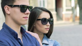 Closeup boy's profile, girl in sunglasses coming and looking aside. Slowly stock footage