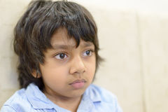 Closeup of boy or student in blue shirt staring at Stock Photos
