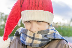 Closeup of boy wearing santa hat, nuzzled into a scarf walking o Stock Photos