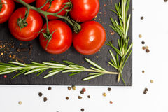 Closeup branch of cherry ripe tomatoes, rosemary, allspice, food photography Royalty Free Stock Photo