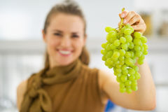 Closeup on branch of grapes in hand of smiling young woman Stock Images