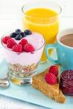 Closeup of breakfast with yoghurt, berries, juice, toast and cof Stock Photos