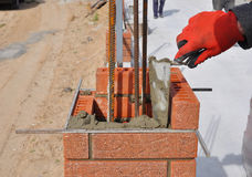 Closeup of a Bricklayer Worker Installing Red Blocks. Bricklaying. Closeup of a Bricklayer Worker Installing Red Blocks and Caulking Brick Masonry Joints Stock Photos