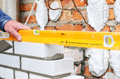A closeup of a bricklayer worker installing wite blocks and caulking brick masonry joints exterior wall with trowel putty knife ou Stock Photos