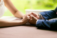 Closeup of bride and groom holding hands on table at restaurant Royalty Free Stock Images