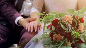 Closeup of bride and groom are sitting and holding hands. Groom holds the bride`s hand stock video footage