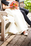 Closeup of bride and groom sitting in a park Royalty Free Stock Photo