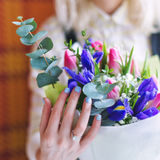 Closeup of bride hands holding beautiful wedding bouquet of roses with her engagement ring on her finger. Selective focus. Royalty Free Stock Image