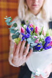Closeup of bride hands holding beautiful wedding bouquet of roses with her engagement ring on her finger. Selective focus. Royalty Free Stock Photos
