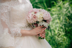Closeup of bride hands holding beautiful wedding bouquet with white and pink roses. Concept of floristics Royalty Free Stock Images