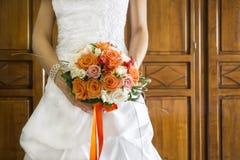 Closeup bride holding bouquet of orange roses stock photography