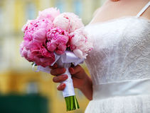 Closeup of a bride holding bouquet of peonies Stock Image