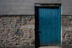Closeup of bright blue door on multi textured concrete/stone wall in the UK royalty free stock photo