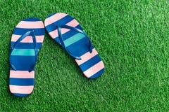 Closeup of bright flip flops on green grass Stock Photography
