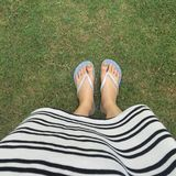 Closeup of bright flip flops and legs on green grass Royalty Free Stock Image