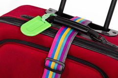 Luggage tag and colorful belt. Closeup of bright green luggage tag and colorful belt on red suitcase stock image