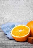 Closeup of bright wholesome orange, wooden board and blue napkin on a light wooden background. A gray wooden table with unpeeled vivid health-giving oranges Royalty Free Stock Images