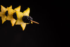 Closeup of a bright yellow wholesome carambola on a stick with a black juicy blackberry on a dark black background. Closeup of juicy blackberries on a stick Royalty Free Stock Photos