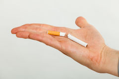 Closeup of broken cigarette on male hand. Stock Images