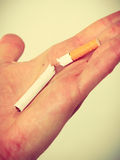 Closeup of broken cigarette on male hand. Stock Photography