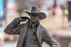 Closeup of a bronze cowboy on a blurry background. Closeup of a bronze cowboy from the Wild West times on a blurry background, USA. In color Stock Photos