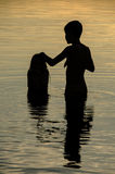 Closeup of brothers in the water of a lake at sunset Royalty Free Stock Image
