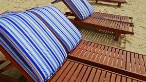 Closeup brown chaise-longues with striped mattresses on beach. Closeup brown wooden chaise-longues with white and blue striped mattresses on clean white sand stock footage