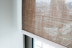 Closeup brown color roller blinds curtains. Sunlight through the windows in the city Stock Photo