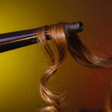 Closeup of brown hair on curler. Haircare, hairstyiling at home concept. Closeup of brown hair on iron curler. Studio shot on dark colorful background stock image