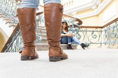 Closeup of brown leather boots and girl sitting in. The background selective focus royalty free stock image