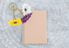 Closeup brown note book with blurred artificial colorful flower on transparent glass bottle on concrete table textured background Royalty Free Stock Images