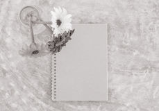 Closeup brown note book with blurred artificial colorful flower on transparent glass bottle on concrete table textured background Royalty Free Stock Image