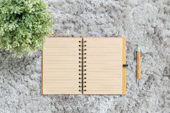 Closeup brown note book with brown pen on gray fabric capet textured background Stock Photo